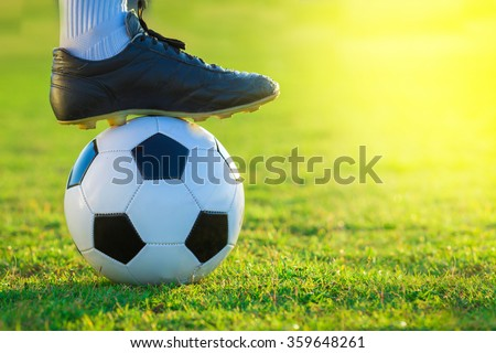 close up of football player tread on the ball on green field