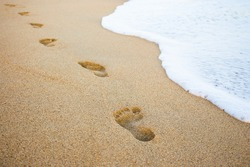 close up of footprints in the sand and sea wave