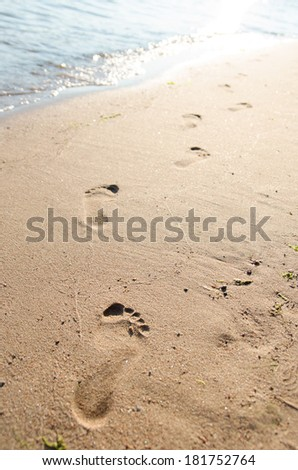 Close up of footprints on the beach sand at the sunset