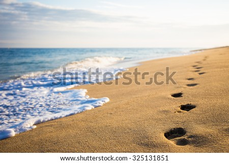 close up of footprints on the beach with golden sand