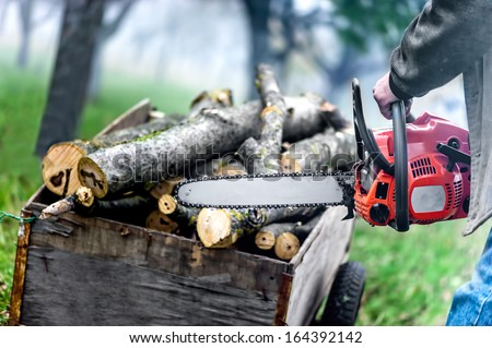 Close up of forest worker, lumberjack with chainsaw against logs and foggy forest background