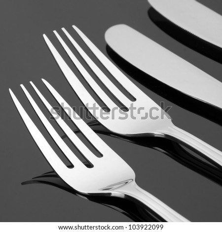 Close-up of forks and knives. In B/W