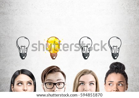 Close up of four business team members faces. They are looking to different directions. There is a large gray wall in the background with light bulbs drawn on it. #594851870