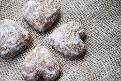 Close-up of four heart-shaped  gingerbread cookies in a sugar glaze lying on a linen cloth top view
