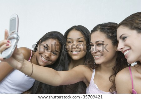 Close-up of four teenage girls taking a picture of themselves with a mobile phone and smiling