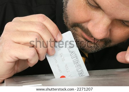 Close up of fourty something man placing credit card into paper shredder.