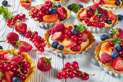 close-up of french desserts - tarts with lemon custard cream filling topped with raspberries, apricots, blueberry, strawberry, red currants and fresh mint on a wooden table