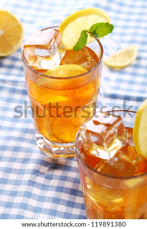 Close up of fresh and cold ice tea with sliced lemon and mint
