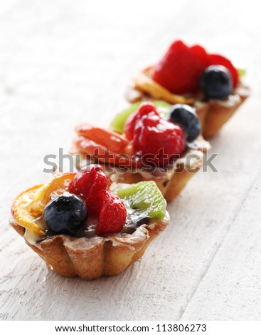 Close up of fresh and tasty cakes with fruits and berries