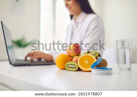 Close-up of fresh apples, kiwis and oranges with measuring tape and glass of clean water on office desk against blurred dietitian with laptop giving online weight loss and healthy diet consultation