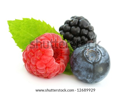 Close-up of fresh blueberry, raspberry, and blackberry with green leaf on white background. Selective focus.