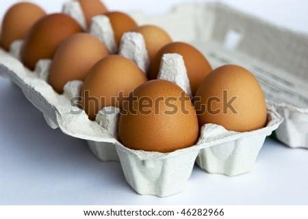 Close up of fresh brown eggs in carton box, selective focus