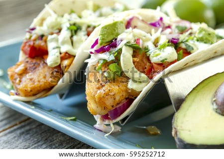 Close up of fresh fish tacos with coleslaw, avocado, salsa and lime creme in a flour tortilla on blue plate