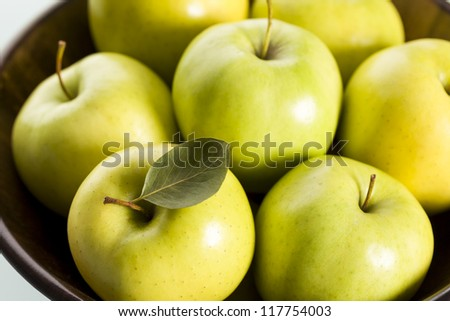 Close up of fresh green golden delicious apples in brown basket, view from top.