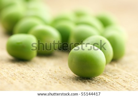 Close-up of fresh green peas on wooden board.