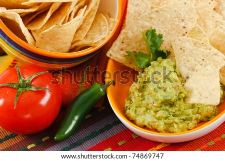 Close up of fresh Guacamole with corn chips, accented with tomato, & jalepeno pepper on a colorful background.