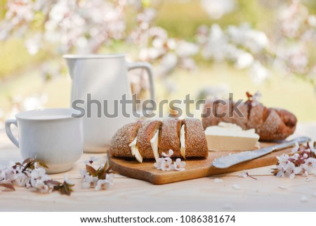 Close-up of fresh homemade bread with butter on wooden board with cold milk in jar and glass outdoor on blurred flowering apple tree branches #1086381674