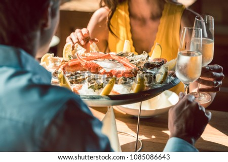 Close-up of fresh oysters and crabs served on ice with lemon at the table of a romantic couple in love, celebrating with champagne at a trendy restaurant