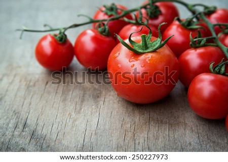 close up of fresh red delicious tomatoes  on an  old wooden tabletop background with place for text