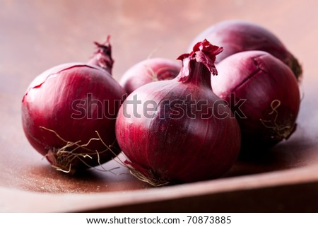 Close-up of fresh red onions on a wooden background