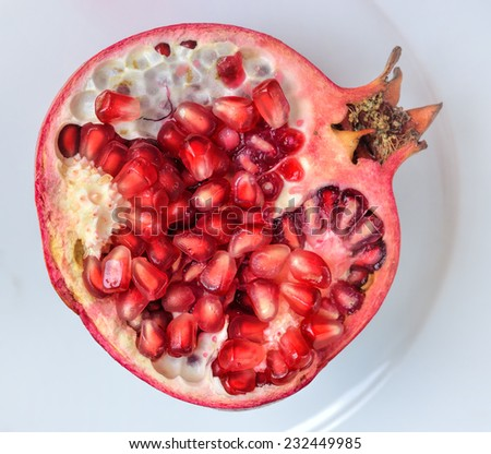 Close up of fresh ripe juicy pomegranate fruit on the white plate isolated on white background, selective focus.