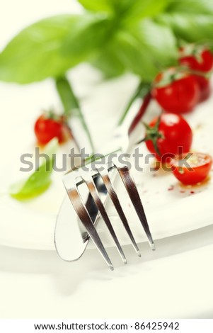 Close up of fresh salad ( cherry tomatoes, basil and drizzling of olive oil), knife and fork