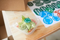 Close up of fresh salad portion in plastic packaging on wooden table in healthy food delivery service, copy space