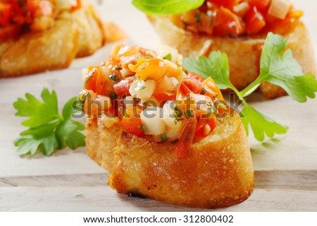 Close Up of Fresh Tomato Bruschetta Appetizers on Crisp Crusty French Baguette Bread Slices Garnished with Fresh Herbs on White Wooden Table Surface