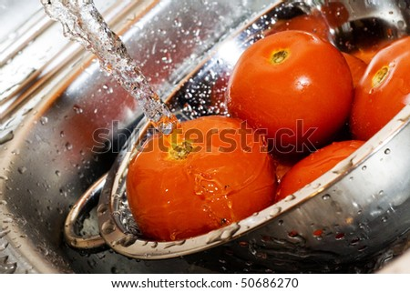 Close-up of fresh tomatos in silver strainer and running water