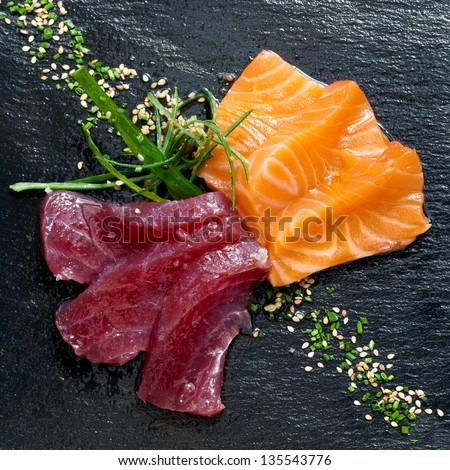 Close up of fresh tuna and salmon sashimi on black plate.