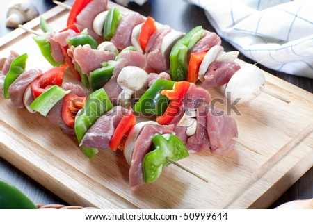 Close up of freshly made meat sticks on wooden board