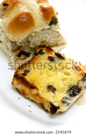 Close up of freshly toasted raisin hot cross buns with melted butter.
