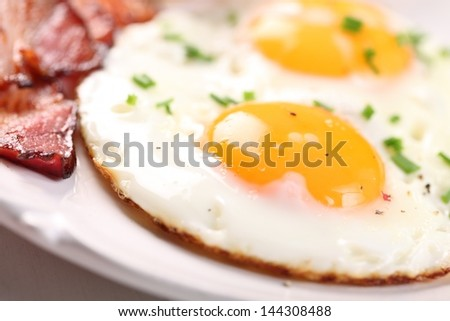 Close-up of fried egg and bacon on plate. Selective focus, shallow DOF