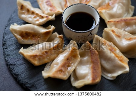 Close-up of fried japanese gyoza dumplings with soy sauce on a stone slate tray, selective focus