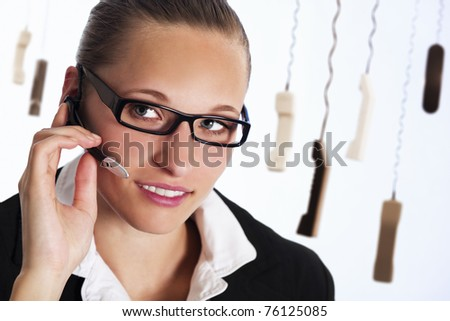 Close up of friendly female phone operator in call centre talking with headset to provide customer service, with many phone receivers hanging in background.