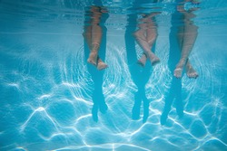 Close up of friends, family legs underwater in the swimming pool with copy space