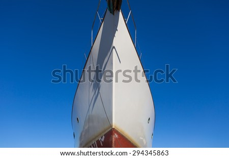 Close up of front side of big ship in port. Ship trunk on blue sky background