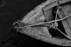 Close up of front side of small fisherman boat moored in port. small row boat floating , view from top angle black and white photography