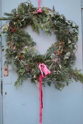 Close up of frost on Christmas festive wreath garland hung on door with white frozen coat of ice on red ribbon bow of the decoration made from hand picked fir tree cones, ivy holly from Winter garden