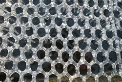 Close up of frozen ice in freezing Winter weather white transparent pattern of hexagons on metal wire covering garden natural pond frost water drips as melts as weather brightens on freezing cold day