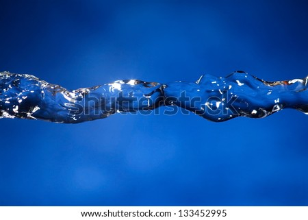 Close-up of frozen water, with beautiful blue background. Great for drink, freshness and cosmetic themes. Taken with technical flash strobe.