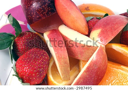 close up of Fruit includes apples,oranges,plums against a white background (looking down)