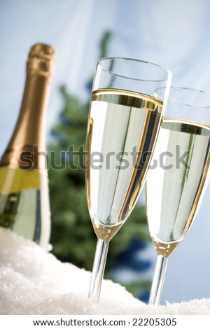 Close-up of full champagne flutes cooling in snow with bottle at background - stock photo