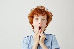 Close up of funny by with curly ginger hair and freckles holding hands near mouth, being shocked seeing adult people kissing.