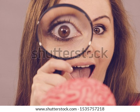 Close up of funny woman holding magnifying glass investigating something and looking closely at fake brain, examing intelligence.