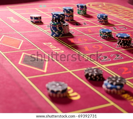 Close  up of gambling chips on red roulette table