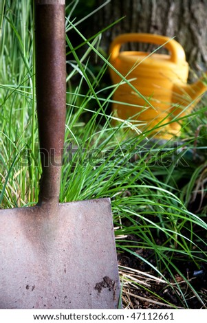 Close up of garden shovel with wateing can in the background