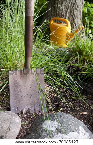 Close up of garden shovel with watering can in the background - stock photo