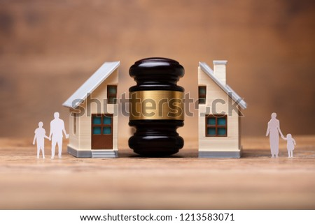 Close-up Of Gavel Between Split Family Figures And House Model On Wooden Desk