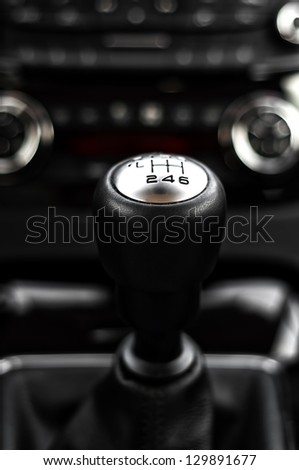 close-up of gearstick inside a car against cockpit and dash